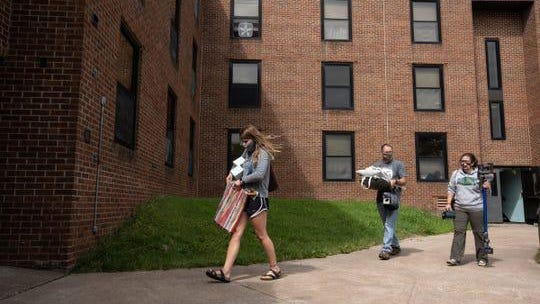 Lake Superior State University junior Rebecca Weipert of Leroy carries her items Wednesday with the help of her father, William Weipert, and mother, Heidi Weipert, at Osborn Hall during a move-in day for students at Lake Superior State University in Sault Ste. Marie.