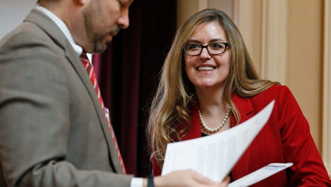 In this Wednesday, April 11, 2018 photo, Virginia State Sen. Jennifer Wexton, D-Loudon, center, talks with Sen. Scott Surovell, D-Fairfax, left, during the Senate special budget session at the Capitol in Richmond, Va. Wexton is one of the candidates in the crowded June Democratic primary that will produce a viable contender in the district representing northern Virginia suburbs and challenge Republican Barbara Comstock.