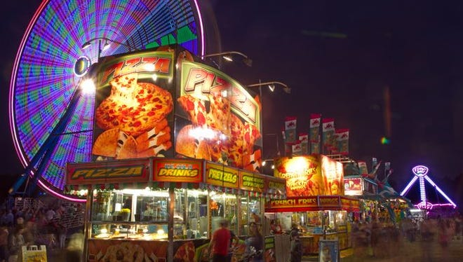 The Wade Shows midway is illuminated by light from distant rides and vendor booths at the Hamburg Family Fun Fest.