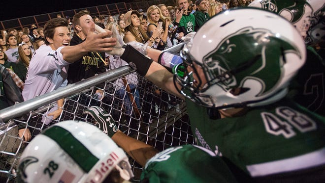 Fossil Ridge High School celebrates with the crowd after a 48-14 win over Far Northeast at French Field Thursday.