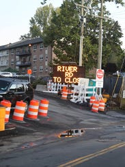 A traffic sign announces plans to close River Road