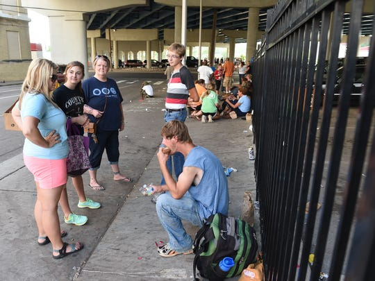 Volunteers Tara Henderlight, and her children Oliver and Desiree, along with Angie Gibson, pass out food to Jeff Flanary, right, near Knox Area Rescue Ministries, July 19, 2016. (AMY SMOTHERMAN BURGESS/NEWS SENTINEL)