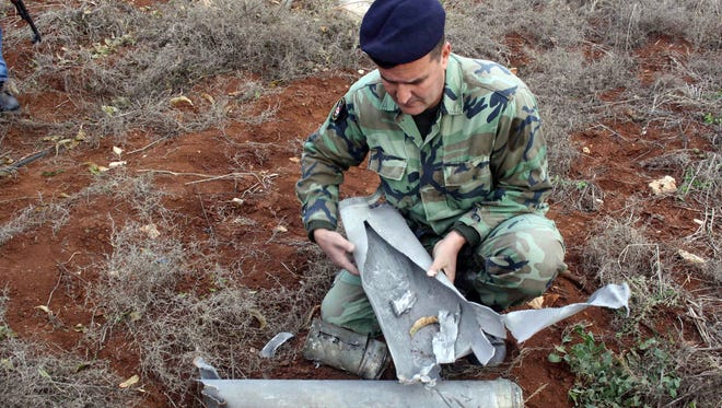 A Lebanese soldier examines of one the shells that was fired by the Israeli army into southern Lebanon on December 29, 2013.