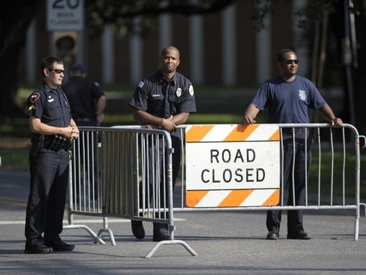 Lafayette Fire Department firefighters stand watch over a road block at the intersection of Taft Street and East Saint Mary Boulevard on the campus of the University of Louisiana at Lafayette in Lafayette, LA, Wednesday, July 16, 2014. Police received reports of suspicious packages near Girard Park and the university campus in Lafayette on Wednesday morning.    Photo by Paul Kieu, The Advertiser