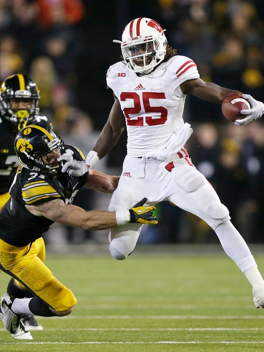 Wisconsin running back Melvin Gordon, right, breaks a tackle by Iowa defensive back John Lowdermilk during the second half of an NCAA college football game, Saturday, Nov. 22, 2014, in Iowa City, Iowa. Wisconsin won 26-24. (AP Photo/Charlie Neibergall)