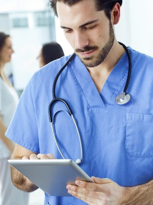 Cheerful young doctor looking at his digital tablet