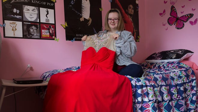 Alyssa Patrias, 20, poses in her bedroom with her evening gown that she wore for the Miss Down River pageant, on Friday, September 9, 2017 in Taylor. She was the first woman with down syndrome to be a contestant in a Miss Michigan preliminary pageant.