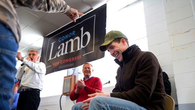 Retired coal miner David Fibazzo, left, of Coal Center places his hat on top of Democratic candidate Conor Lamb's head during a rally with the United Mine Workers of America on March 11, 2018, in Waynesburg, Pa.