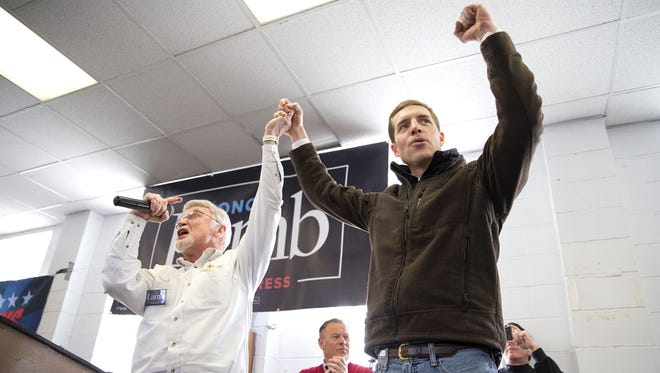Cecil Roberts, president of the United Mine Workers, left, lifts up Democratic candidate Conor Lamb's hand during a rally, March 11, 2018, at the Greene County Fairgrounds in Waynesburg, Pa.