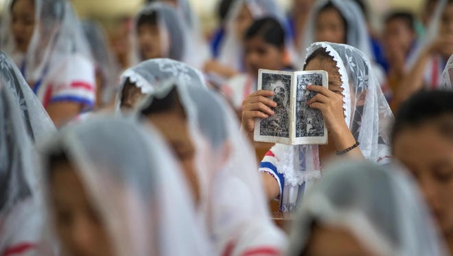 This photo taken on Nov. 19, 2017 shows a Catholic devotee in a congregation holding up a prayer book during a Sunday service at the St. Francis Roman Catholic Church in Hpa-an in Myanmar's Karen State.