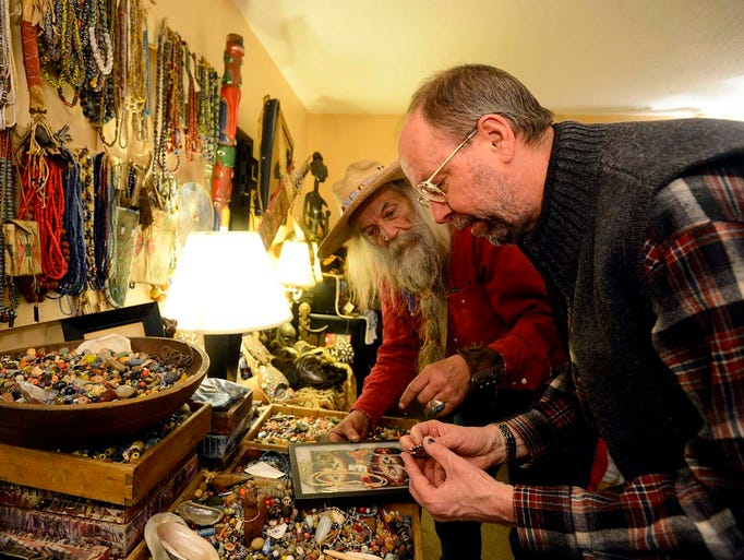 Ray Geyer, right, makes a purchase from artist Leo Hakola during the March in Montana show at the Town House Inn on Friday afternoon.