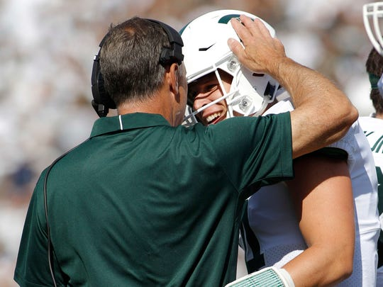 Michigan State quarterback Brian Lewerke, right, is congratulated by head coach Mark Dantonio after scoring a 61-yard rushing touchdown against Western Michigan during the first quarter on Saturday, Sept. 9, 2017, in East Lansing.
