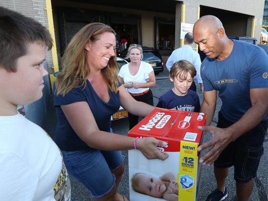 Lisa Walsh of Mamaroneck, with her sons Peter, left, and Daniel Walsh donate goods to Mariano Rivera for hurricane relief at Steiner Sports in New Rochelle.