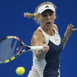 Caroline Wozniacki of Denmark returns a shot against Angelique Kerber of Germany during the Women's singles Second round match on day five of the 2015 China Open at the China National Tennis Centre