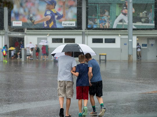 Fans make their way between the bathrooms and Lamade Stadium, background, Sunday afternoon before all play was cancelled for the day at the Little League World Series.