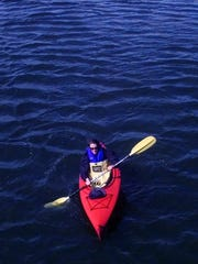 A kayaker takes in the sun on Lake Champlain.