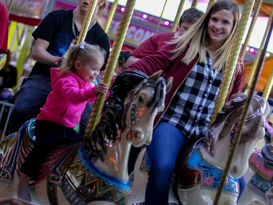 People ride the merry-go-round during the 83rd annual
