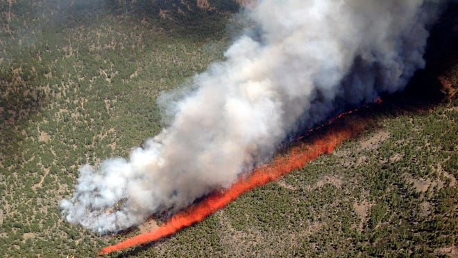 A June photos shows an MD-87 air tanker laying a line of retardant to flank the Two Bulls Fire burning at the Deschutes National Forest near of Bend, Ore.