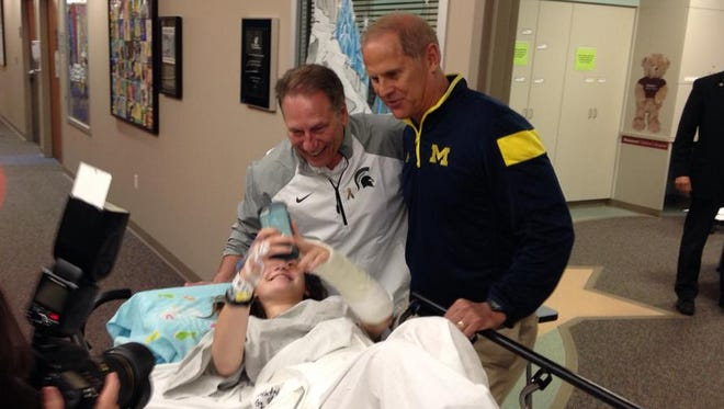 Michigan State basketball coach Tom Izzo, center, and Michigan basketball coach John Beilein, right, pose for a photo with a patient Natalie Jacobson of Bloomfield Hills on Monday, June 1, 2015.