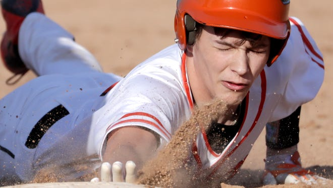 Kaukauna's Kolbe Pike dives back to first base against Oshkosh North during a Fox Valley Association baseball game at Bayorgeon Field in Kaukauna.