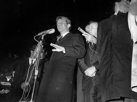 Senator Robert F. Kennedy (D-N.Y.) looking pale and shaken at the news of Martin Luther King's assassination, disreguarded his prepared speech and spoke briefly to a predominantly black crowd of 2,500 here last night, urging them not to meet violence with violence.
