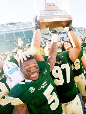 Kapri Bibbs (5) and Calvin Tonga (97) hold the Ram-Falcon Trophy high above their heads after winning it back from Air Force in a 2013 game at Hughes Stadium. CSU doesn't have any of the three traveling trophies it plays for each year right now, but can win two of them back the next two weeks.