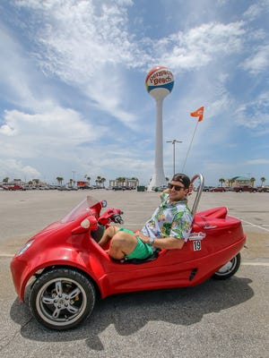 News Journal reporter Brian Achatz test drives a Scoot Coupe rented from Scooter Hut Rentals on Pensacola Beach on Thursday, June 21, 2018. Manufactured by Panther Motors in Tamarac, Fla., the three-wheeled gas-powered vehicles are street legal, seat two adults, and have a small storage space behind the passengers.