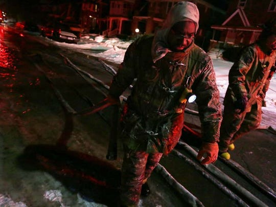 Firemen have to quickly fold and load their water hoses back onto their trucks after fighting a fire as they turn into ice because of the single-digit temperatures on Detroit' swest side.