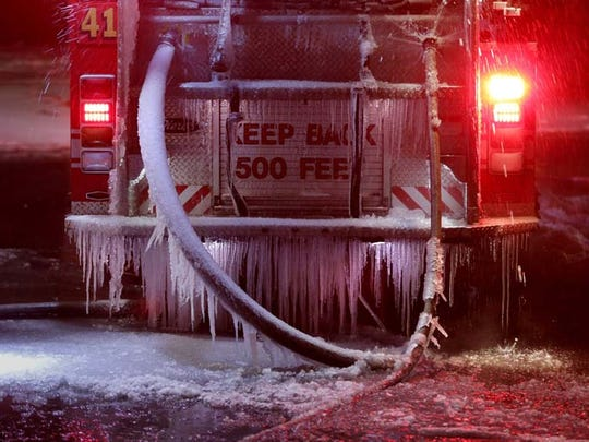 Detroit Engine 41 starts to be enclosed in ice as firefighters battle a fire on Monday, Feb. 23, 2015.