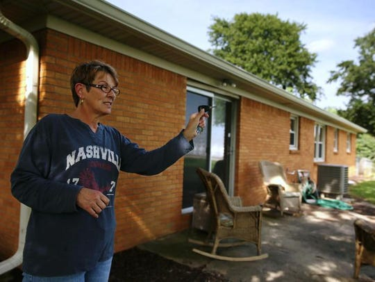 Sandy Morgan in the backyard of her new home in Greenfield.