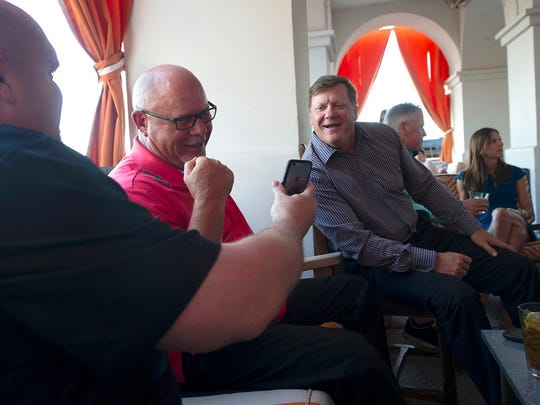 """Steve Keim, left, shows Bruce Arians, center, and Tom Marreel, a text from country singer Blake Shelton while the trio are at the Living Room Wine Cafe Lounge in Chandler, AZ, on Wednesday, June 3, 2015. Keim and Arians, natives of York County, were named NFL Executive and Coach of the Year for their work with the Arizona Cardinals during the 2014 season. Jason Plotkin - Daily Record/Sunday News"""