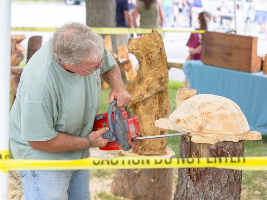 Jake Albright, of Hanover, uses a chainsaw while carving