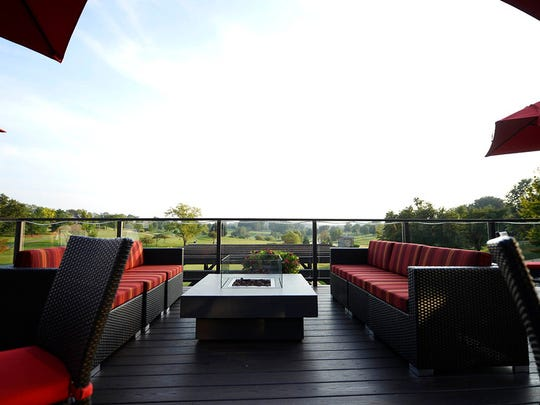 """A firepit is flanked by two couches on the deck patio at oak., the recently opened restaurant at Heritage Hills in York Township Thursday, September 3, 2015. Formerly Ironwoods, oak. features deck patio seating, a double-sided bar with 12 taps, and a new food and drink menu in a more casual dining environment."