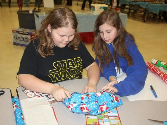 Kylee Vice (left) and Karlee Vice, sixth graders at Clear Creek Amana Middle School, help wrap a gift during Wrappin for a Cause Thursday, Dec. 17, at the school in Tiffin.