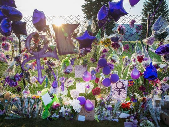 Mementos left by fans are attached to the fence which