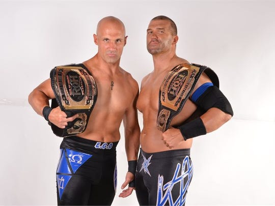 """""""The Addiction"""" tag team duo poses with their Ring of Honor title."""