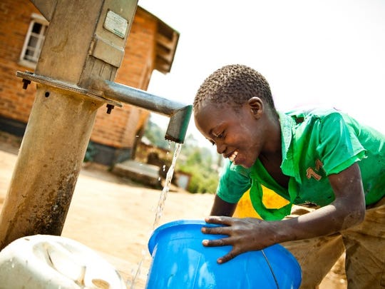 A child retrieves water from a well in Malawi. Funds for the well were raised by nonprofit coffee shop The Well, which will open a location in Fishers in mid-August.
