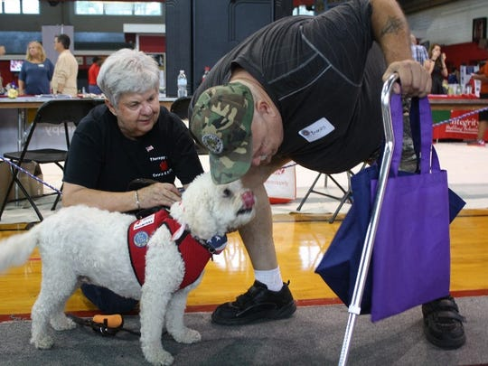 Marine veteran Brooks Vermillion stoops for a kiss from a Red Cross therapy dog the Jeffersonville Stand Down at the Nachand Fieldhouse.