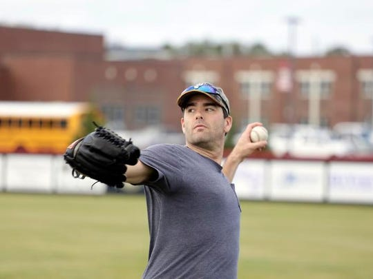 Major League Baseball player Seth Smith practices on the baseball field at Germantown High School.
