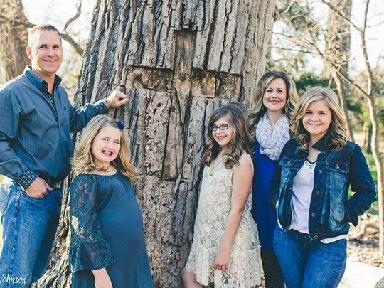Author Christy Beam and her family pose by the cottonwood tree by their home where a miracle saved daughter Annabel (center, in white dress), not only from a 30-foot fall but from an incurable digestive disorder.