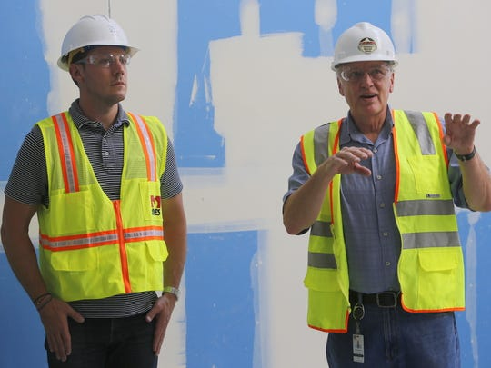 Jeremy Trumble of FBT Architects, left, listens as Ted Lasiewicz, the director of operations for the Farmington Municipal School District, describes one of the features of the new main building at Farmington High School during a tour on Thursday.
