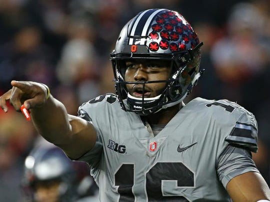 Buckeyes quarterback J.T. Barrett (16) signals to his