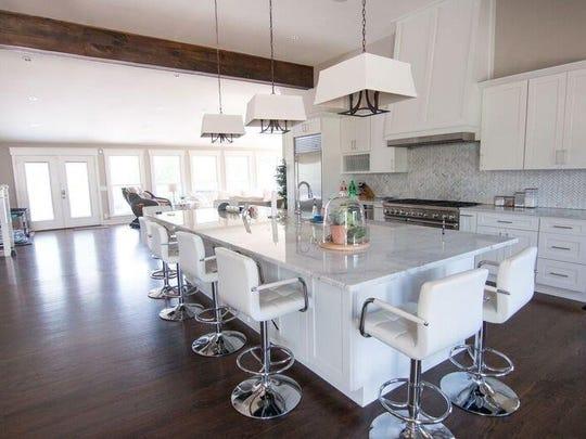 The contemporary kitchen boasts Corian marble countertops, custom cabinets, a Sub-Zero refrigerator and Thermador range.