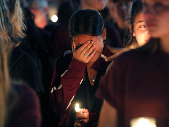 A woman cries during a candlelight vigil for the victims