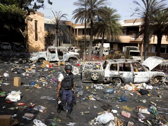 Vehicles sit charred and looted merchandise lies scattered