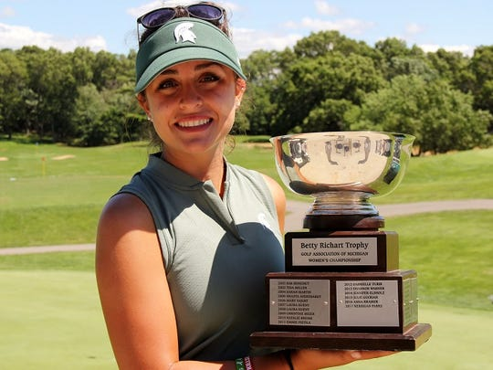 Allyson Geer of Brighton holds the trophy for winning the Golf Association of Michigan Women's Championship.
