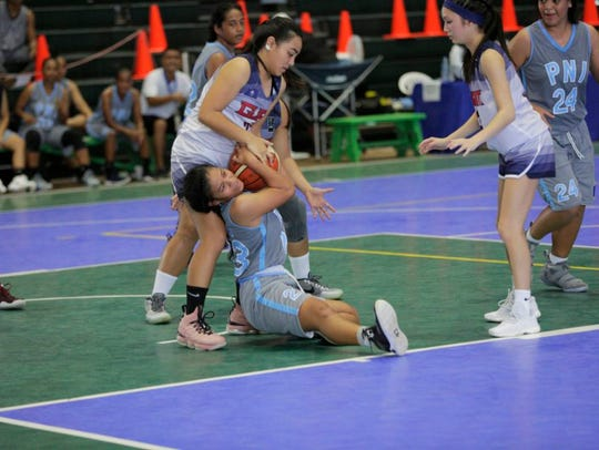 Team Guam's Rosita Duenas, standing, tries to wrest