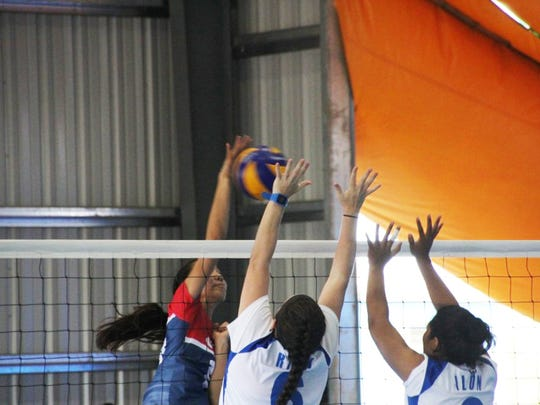 Lori Okada goes over and through the Marshall Islands' block during women's volleyball action at the Micronesian Games in Yap.