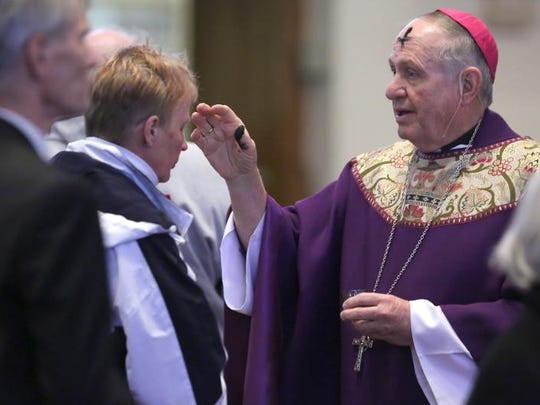 Bishop Richard E. Pates places a cross of ashes on a worshipper's forehead Wednesday March 5, 2014, during an Ash Wednesday service at Saint Ambrose Cathedral in Des Moines, Iowa.