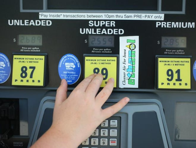 b0716ethanol-Zach Tuttle, 12, helps his mother Cheri pump ethanol at a HyVee in West Des Moines on Thursday. Tuttle, of Earlham said she doesn't worry about which blend of gas she buys but usually checks to make sure she gets the cheapest of her choices. Mary Chind/The Des Moines Register